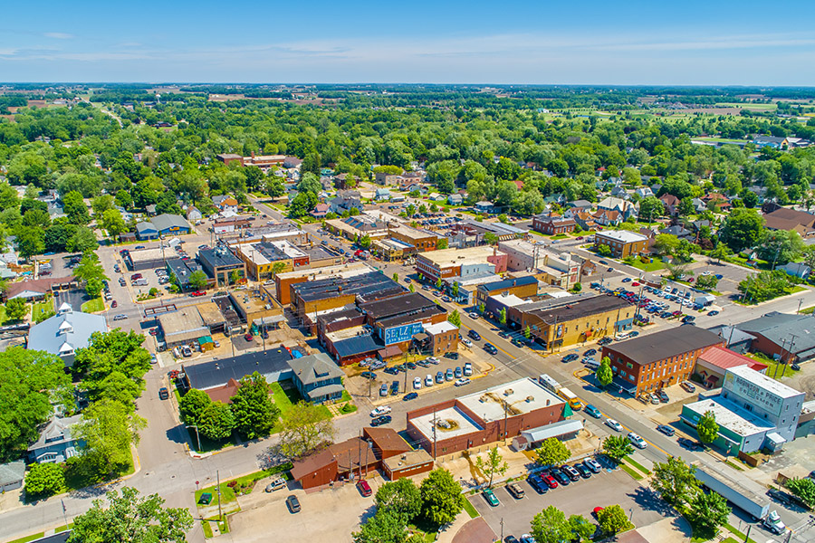 Contact - Aerial View of Small Town in Indiana with Trees, Communities and Farms in the Distance on a Bright Sunny Day